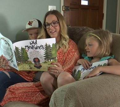 woman reads book to children
