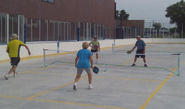 Mixed doubles group playing pickleball