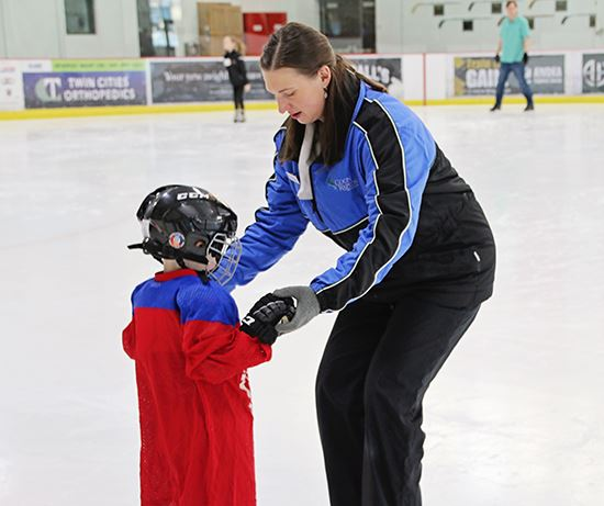 Skating School Instructor helping young skater